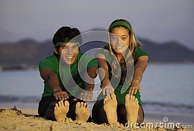 Couple exercising on beach at sunrise