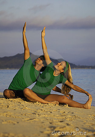 Couple exercising on beach at sunrise