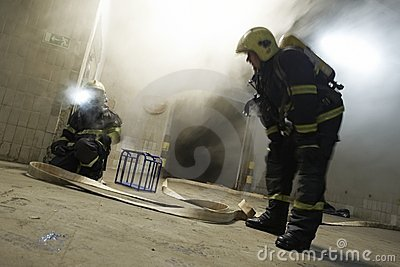 The couple of firemen fighting with the fire Editorial Stock Image