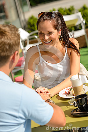 Couple flirting holding hands at cafe bar