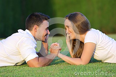 Profile of a couple in love flirting and looking each other lying on