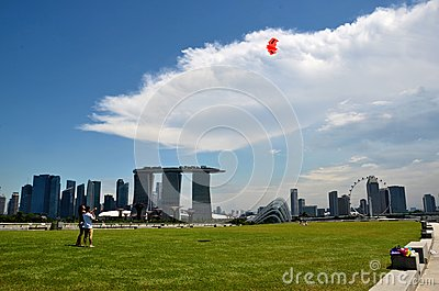 Couple flying kite infront of Marina Bay Sands, Singapore Editorial Stock Image