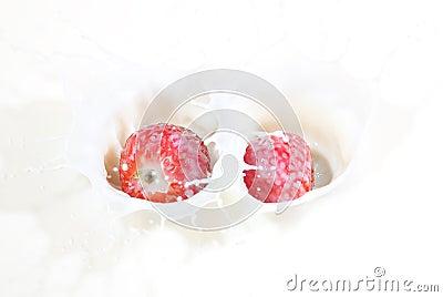 A couple of fresh strawberries splashing into milk