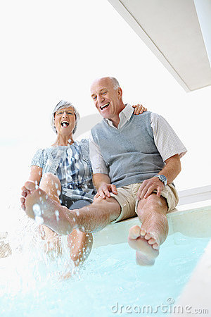 Couple frolicking by the swimming pool
