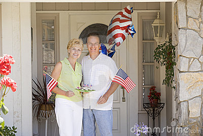 Couple at front door on fourth of July with flags