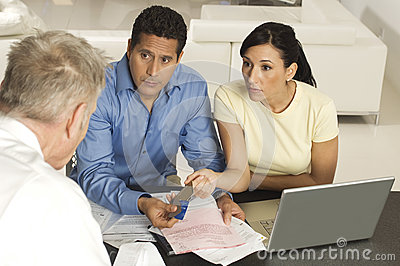 Couple Giving Documents And Credit Cards To Advisor