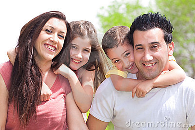 Couple giving two young children piggyback