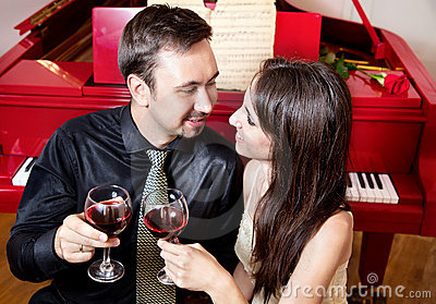 Couple with glasses of wine near piano