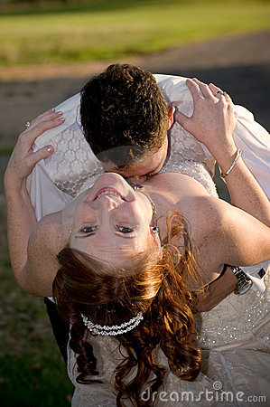 Couple with groom kissing bride in the cleavage
