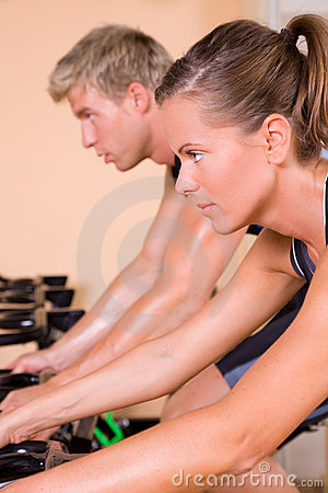 Couple in the gym cycling