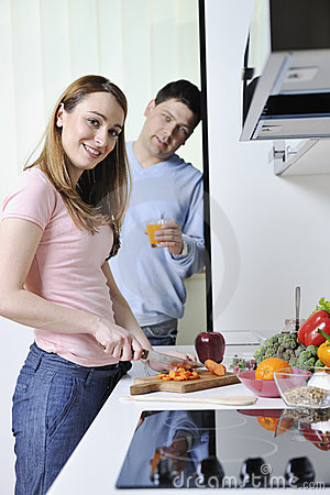 Couple have fun preparing healthy food in kitchen