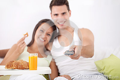 Couple having breakfast and watching TV