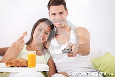 Couple having breakfast and watching TV