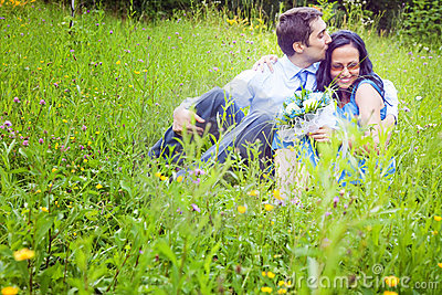 Couple having a candid romantic kiss in the grass