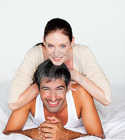 Couple having fun in bed looking at the camera