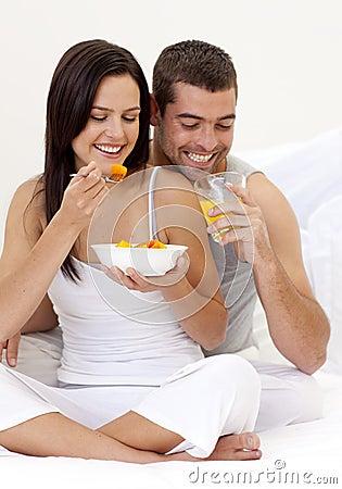 Couple having nutritive breakfast in bed