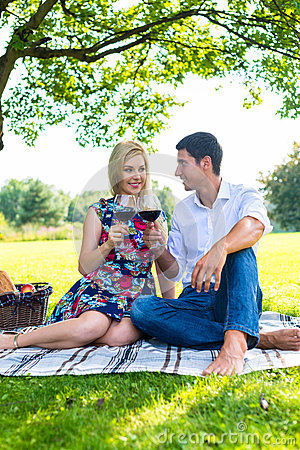 Couple having picnic wit red wine on meadow stock photo for Youporn piscine