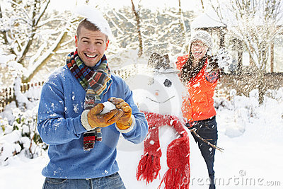 Couple Having Snowball Fight In Garden