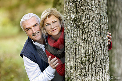 Couple hiding behind tree