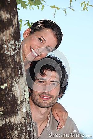 Couple hiding behind tree