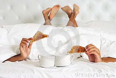 Couple Hiding Under Duvet Enjoying Breakfast In Bed
