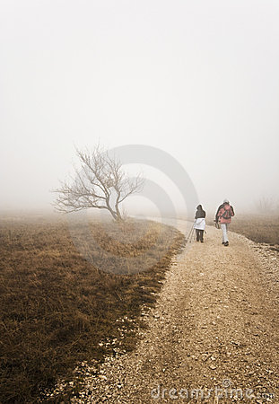 Couple hiking uphill on a bad weather day