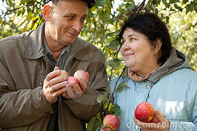 Couple hold apples and look against each other