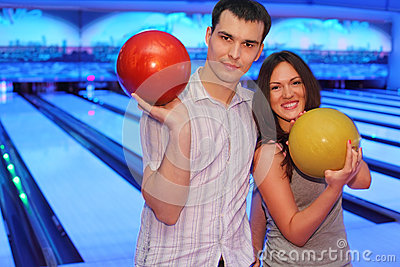 Couple hold balls in bowling club