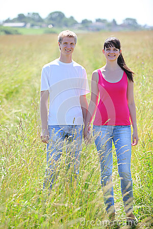 couple hold hands in field near village