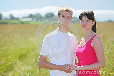 Couple hold hands, grass in field near village