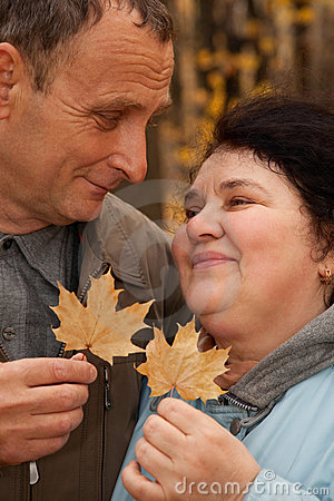 Couple hold leaves and look against each other