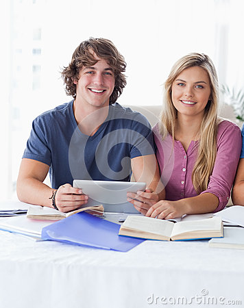 A couple hold a tablet together