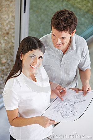 Couple holding architectural drawing