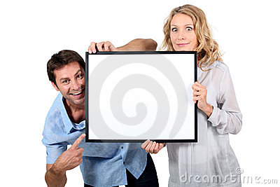 Couple holding blank picture frame