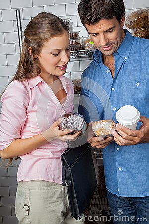 Couple Holding Cakes And Coffee Cup At Grocery