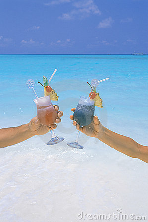 Couple holding cocktail in tropical beach maldives