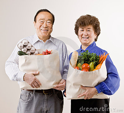 Free Couple Holding Grocery Bag Full Of Fruit Stock Image - 6599921