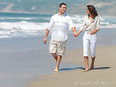 Couple holding hands on beach, walking.