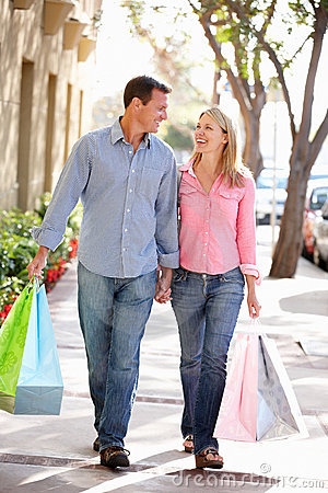 Couple holding hands carrying shopping