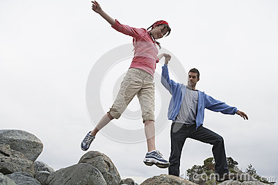 Couple Holding Hands And Jumping On Rocks