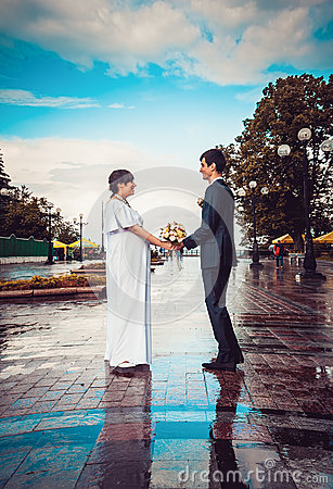 Couple holding hands on wet road against blue sky