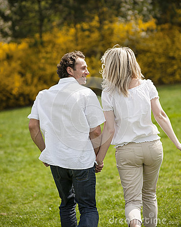 Free Couple Holding Hands With Back To Camera Running Through Park Royalty Free Stock Photos - 31843258