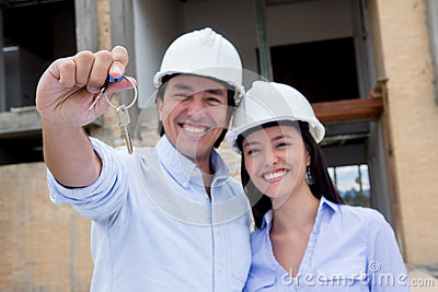Couple holding keys to their house