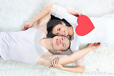 Couple holding red heart together lie in a bed