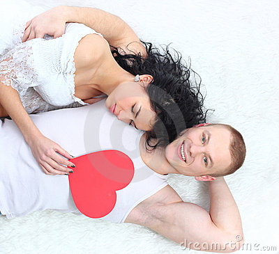 Couple holding red heart together lying