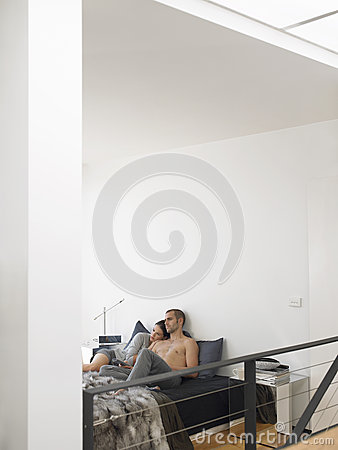 Couple Holding Remote Control In Bed