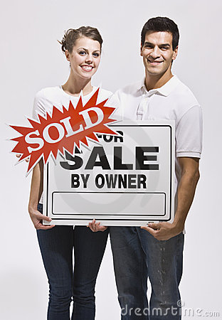 Couple Holding For Sale By Owners Sign