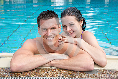 Couple in holidays posing at hotel pool edge