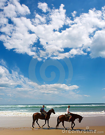 Couple of horse riders on beach
