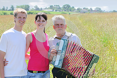 Couple hug near grandfather plays on accordion